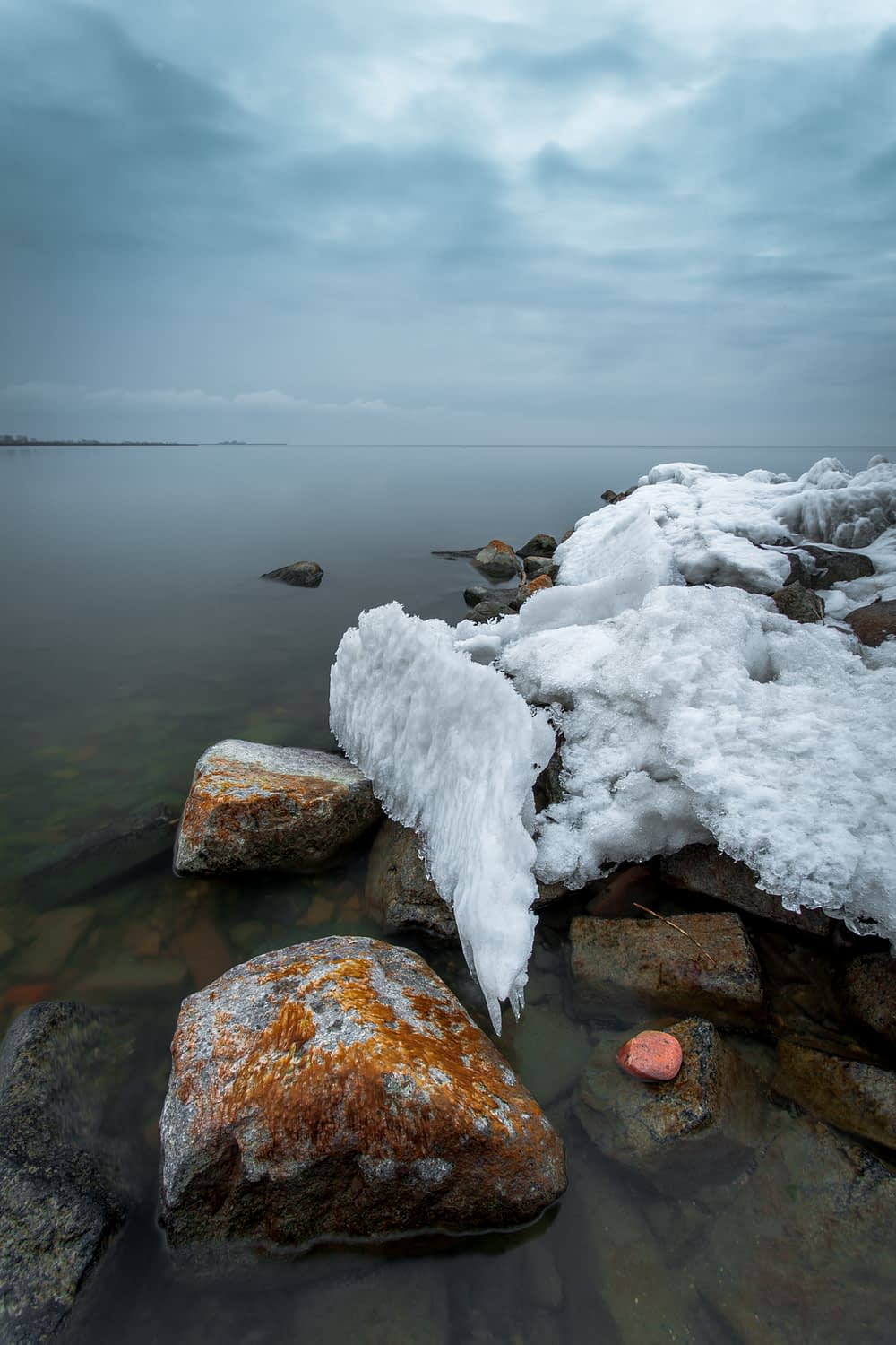 A landscape photograph of the Dutch coast with ice covered rocks in the foreground.